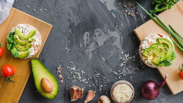 Desayuno saludable con aguacate; ajo; arroz; tomate cherry y cebolla en textura de cemento Foto gratis