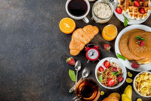 Desayuno saludable concepto de comer varios alimentos de la mañana - panqueques waffles croissant sándwich de avena y granola con yogur fruta bayas café té jugo de naranja fondo oxidado oscuro Foto Premium