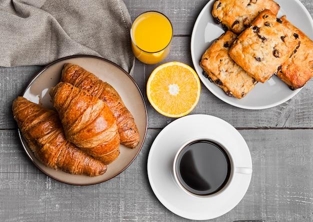 Desayuno saludable con jugo de café frutas pastelería en mesa de madera Foto Premium