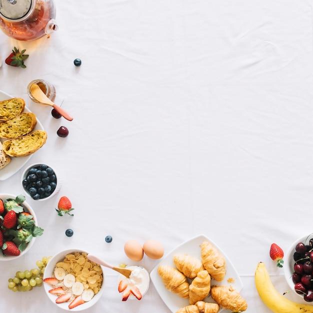 Desayuno saludable por la mañana en un mantel blanco con espacio para texto Foto gratis