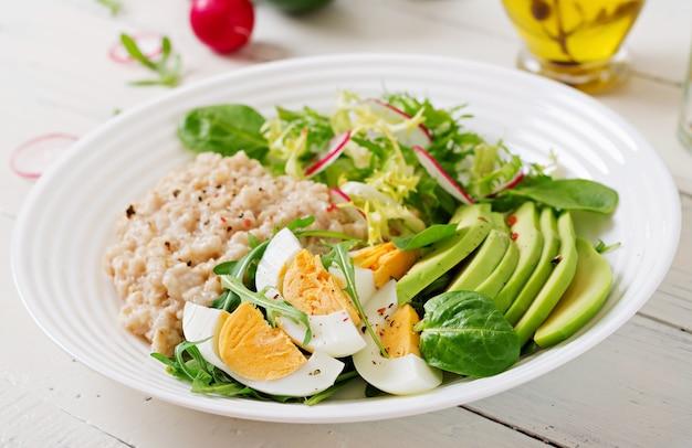 Desayuno saludable. menú dietético gachas de avena y ensalada de aguacate y huevos. Foto gratis