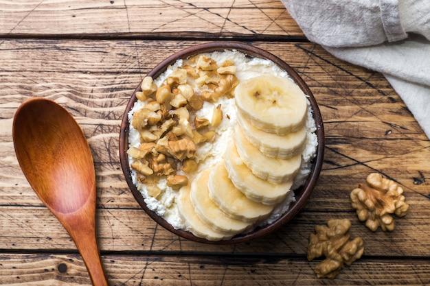 Desayuno saludable. requesón con plátano y nueces sobre fondo de madera. Foto Premium
