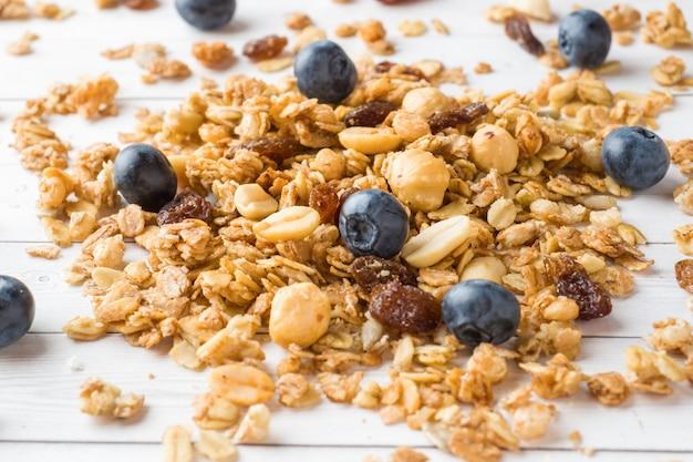 Desayuno seco de copos de avena, gránulos y frutos secos. muesli en una mesa de luz con arándanos Foto Premium