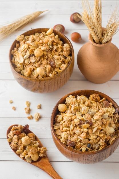Desayuno seco de copos de avena, gránulos y frutos secos. muesli en un plato profundo de madera. Foto Premium
