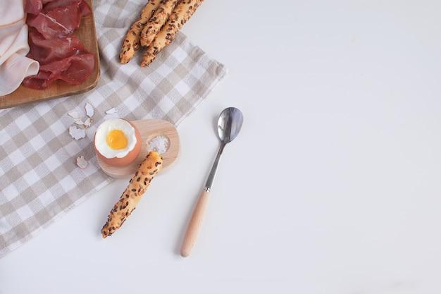 Desayuno servido huevo cocido en huevera de madera Foto Premium