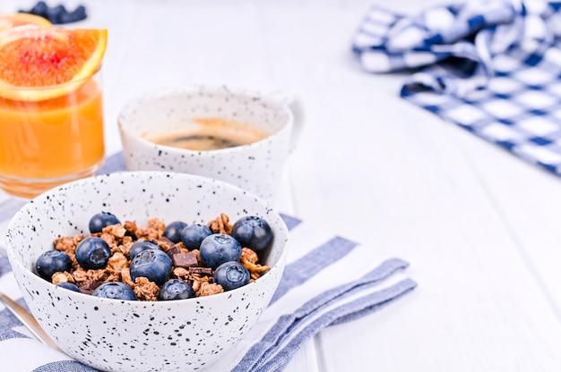 Desayuno sobre un fondo blanco de madera. muesli con bayas y jugo de naranja. copia espacio Foto Premium