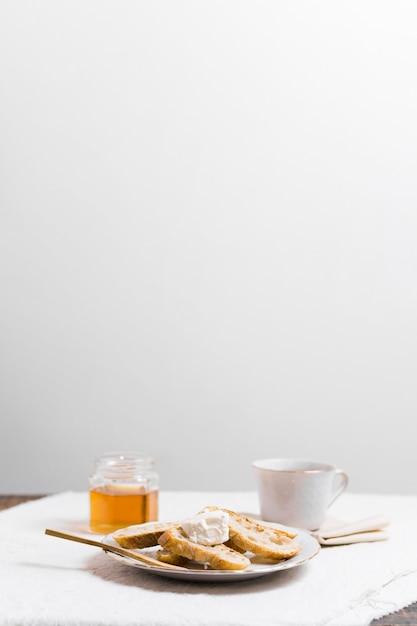 Desayuno sofisticado con taza de té y miel. Foto gratis