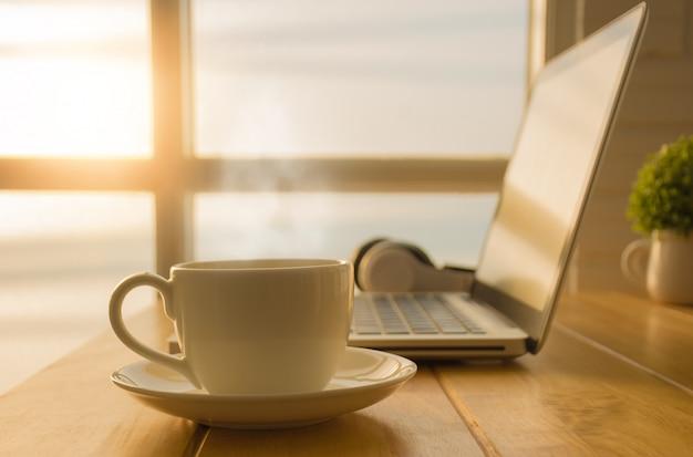 Desayuno con una taza de café caliente sobre la mesa en la oficina que tiene una computadora portátil. Foto Premium