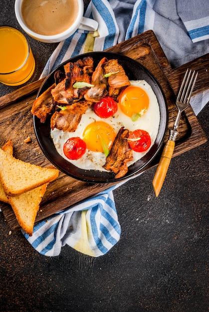 Desayuno tradicional inglés casero, huevos fritos, tostadas, tocino, con taza de café y jugo de naranja. Foto Premium