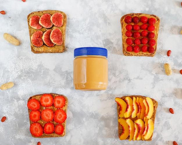 Desayuno tradicional de verano americano y europeo: sándwiches de pan tostado con mantequilla de maní, copia vista superior Foto gratis