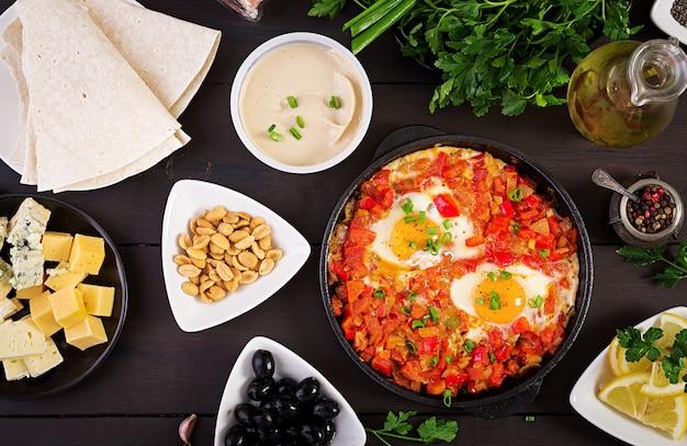 Desayuno turco shakshuka, aceitunas, queso y fruta. rico brunch. Foto gratis