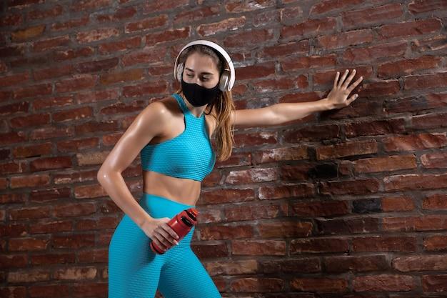 Descansando. atletas profesionales entrenando en pared de ladrillo con máscaras faciales. deporte durante la cuarentena de la pandemia mundial de coronavirus. pareja joven practicando en el gimnasio con equipo seguro. Foto gratis