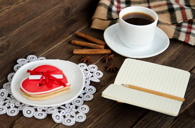 Descanso acogedor. taza de café, pan de jengibre en forma de corazón, bloc de notas con lápiz, especias Foto Premium