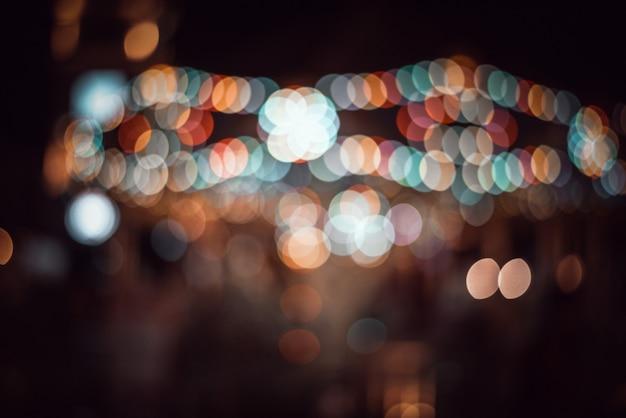Desenfocada vida nocturna de la ciudad: coches, gente y farolas, estilo retro Foto Premium