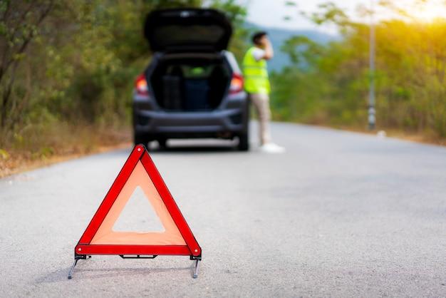 Desglose triángulo firme en la carretera con un hombre asiático preocupado hablando por teléfono móvil con una compañía de seguros o centro de servicio de automóviles después de la avería del automóvil en la carretera Foto Premium