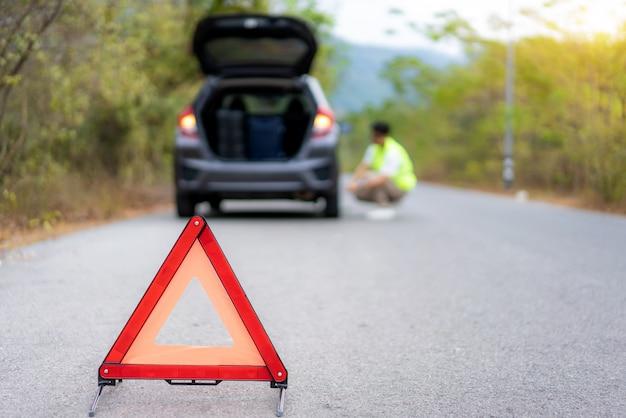 Desglose triángulo firme en la carretera con un hombre asiático preocupado reparando y cambiando neumáticos mientras espera un seguro o un centro de servicio de automóviles Foto Premium