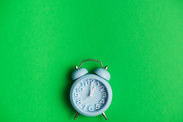 Despertador azul contra fondo verde Foto gratis