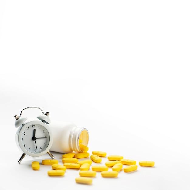 Despertador blanco y píldoras amarillas derramadas sobre fondo blanco. Foto gratis