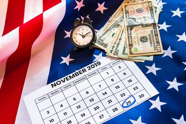 Despertador y calendario con 29 de noviembre de 2019, viernes negro, bandera estadounidense y dinero. Foto Premium