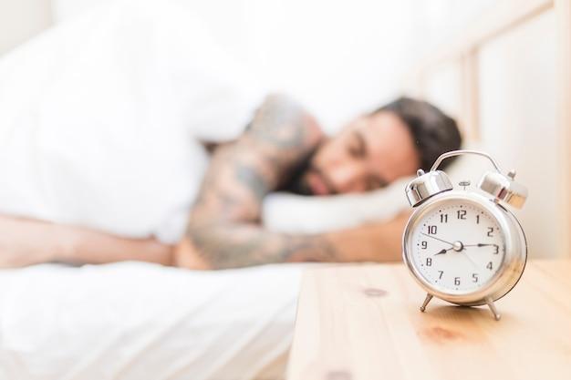 Despertador en el escritorio de madera con hombre durmiendo en el fondo Foto gratis