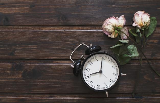 UN  SABIÁ  CANTA  Y  SALUDA  LA  PRIMAVERA.... Despertador-negro-mesa-madera-oscura-dos-rosas-secas_28632-65