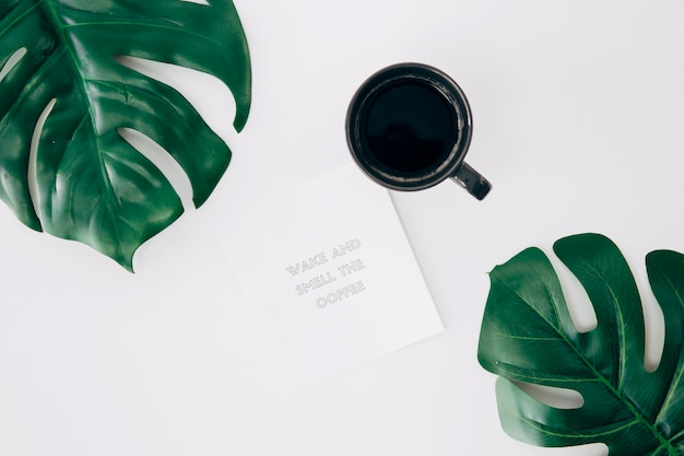 Despierte y huela el mensaje de café en la nota cerca del café y las hojas de la monstera en el escritorio blanco Foto gratis