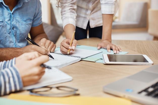 Detalle del equipo trabajando en un nuevo proyecto en el espacio de coworking, escribiendo ideas, mirando gráficos en la tableta y la computadora portátil. trabajo en equipo, concepto de negocio. Foto gratis