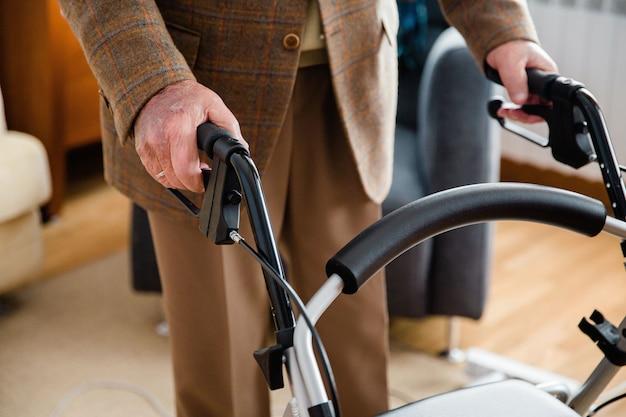 Detalle de la mano de un anciano que usa un andador para moverse por la casa. Foto Premium