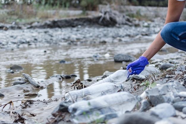 Detalle de una mano recogiendo una botella de plástico en el río. Foto Premium