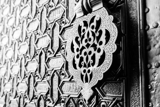 Detalle de un martinete de puerta islámica y adornos fuera de una de las puertas de entrada principal a la catedral de sevilla, españa. Foto Premium