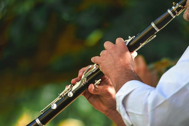 Detalle de un músico callejero tocando el clarinete Foto Premium