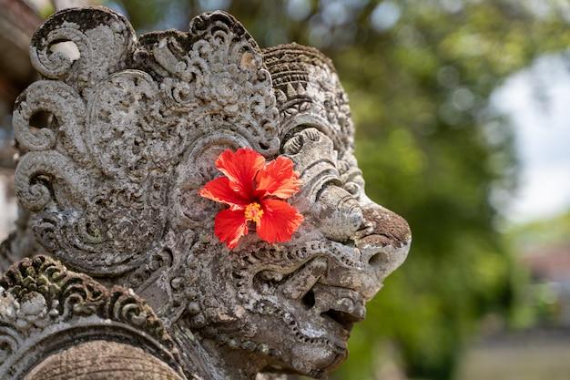 Detalle del perfil de la parte superior de una estatua de piedra en un templo hindú con una flor roja Foto Premium