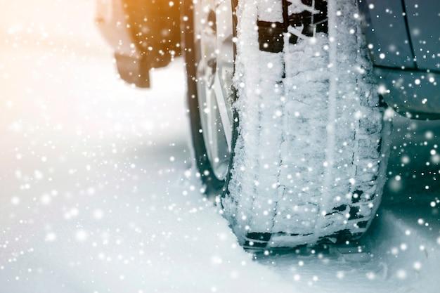 Detalle de la rueda del coche con el nuevo protector de neumáticos de goma negra en la carretera nevada de invierno transporte y seguridad. Foto Premium