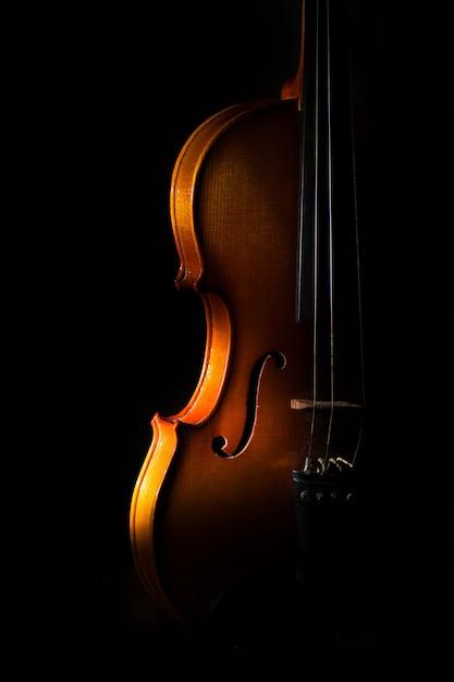 Detalle de violín sobre un fondo negro entre luces o sombras Foto Premium