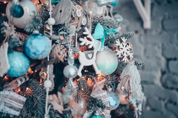 Detalles de un árbol de navidad decorado en turquesa oscuro y naranja con venado de juguete blanco Foto Premium