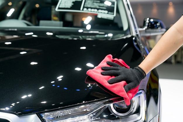 Detalles del coche: el hombre sostiene la microfibra en la mano y pule el automóvil. Foto Premium