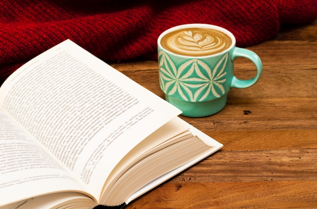 Detalles de naturaleza muerta, taza de café con leche o café capuchino con un libro y suéter rojo sobre una mesa de madera. Foto Premium