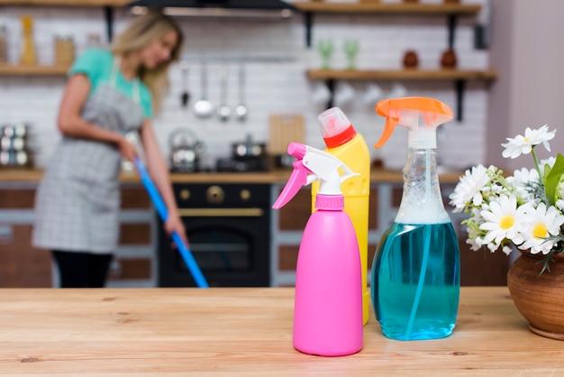 Detergente y botellas de spray en el escritorio de madera delante de mujer deprimida en casa Foto gratis