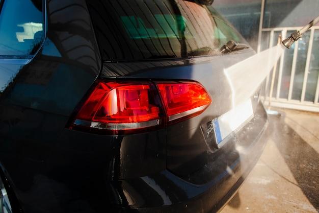 Detrás de un automóvil negro limpiado con agua Foto gratis