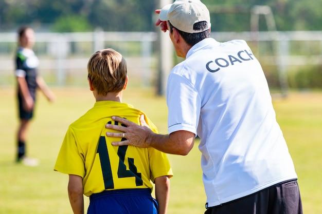 Detrás del entrenador de fútbol masculino a punto de enviar a su joven jugador en el juego Foto Premium