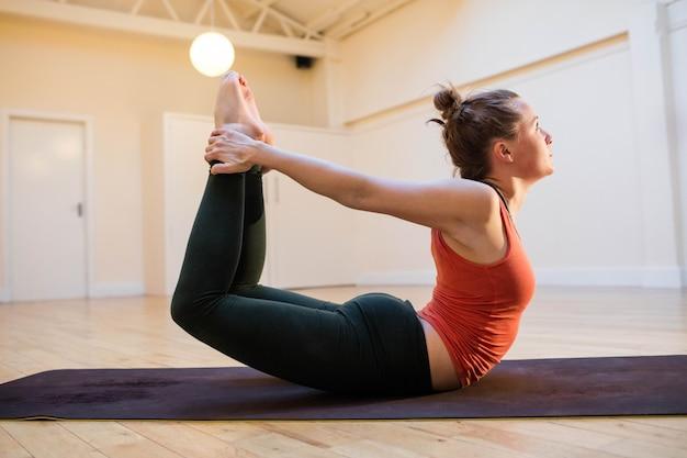 Dhanurasana mujer que realiza plantean en la estera de ejercicio