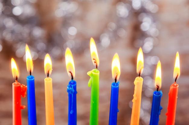 Día de fiesta judío menorah hermoso con las velas ardientes en fondo borroso luz. Foto Premium