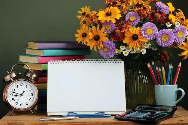 Día del maestro, 1 de septiembre. para volver a la escuela. ramo de flores de otoño, reloj despertador y un álbum al aire libre con una espiral en la base Foto Premium
