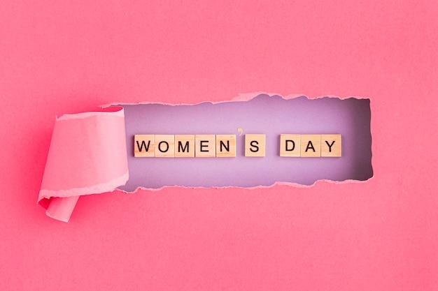 Día de la mujer escrito en letras de scrabble y papel rasgado. Foto Premium