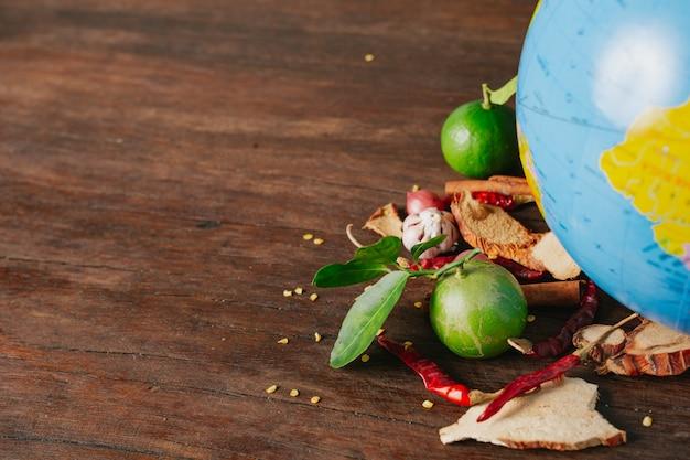 El día mundial de la alimentación, una especia repleta de automóviles y colores frescos colocados en un globo simulado sobre un piso de madera marrón. Foto gratis