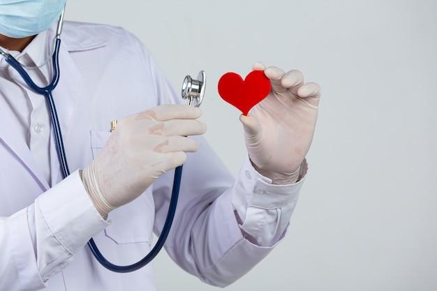 Día mundial de la diabetes; docter con estetoscopio y forma de madera de corazón rojo Foto gratis