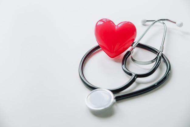 Día mundial de la salud. corazón rojo con estetoscopio en blanco Foto Premium