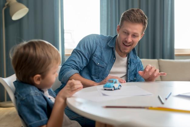 Día del padre, padre e hijo jugando con un auto Foto Premium
