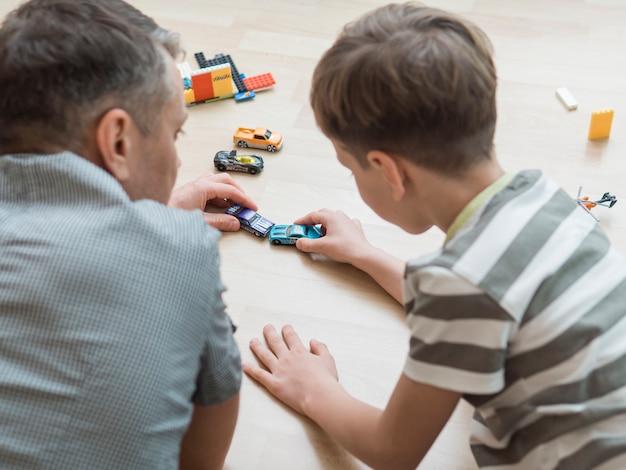 Día del padre papá e hijo jugando con autos en el piso Foto gratis