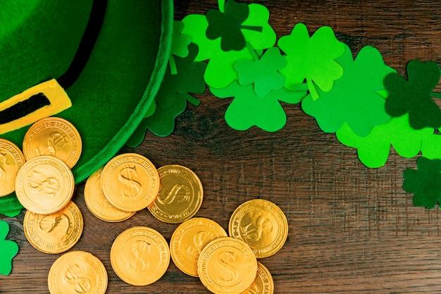 Día de san patricio. monedas de oro, trébol verde de tres pétalos, sombrero verde de duende en mesa de madera Foto Premium
